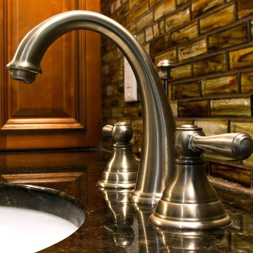 A Picture of a Faucet with a Granite Countertop Underneath it.