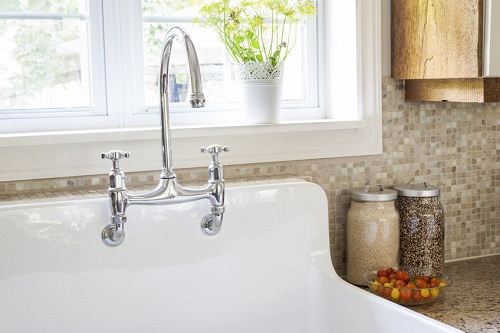 A Sink With Tile Backsplash in the Background
